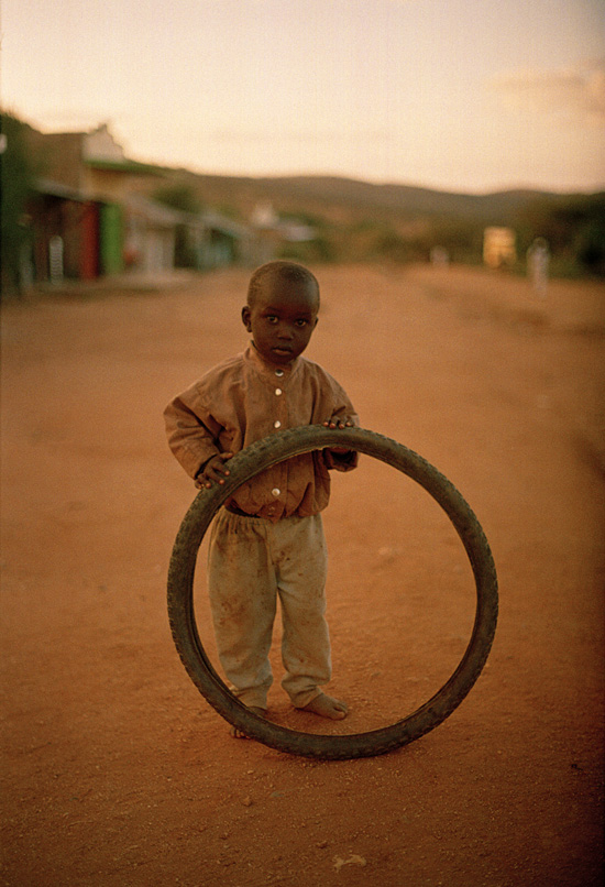 Boy playing with a bicycle tire in Ol'doinyo