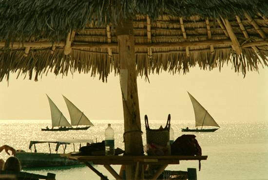 Outriggers sail along the beaches of Kenya