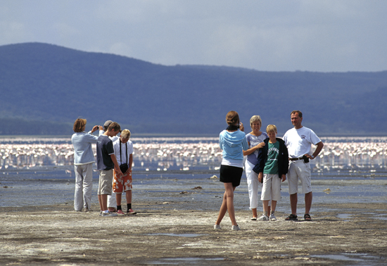 Tourists at lake Nakuru on a backgrund of flamingos