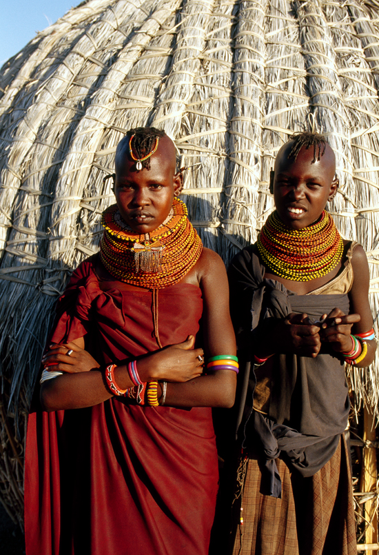 Turkana girls in traditional clothes in front of house
