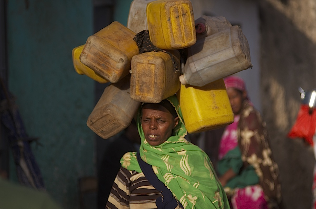 Woman in Harar carrying plastic cans