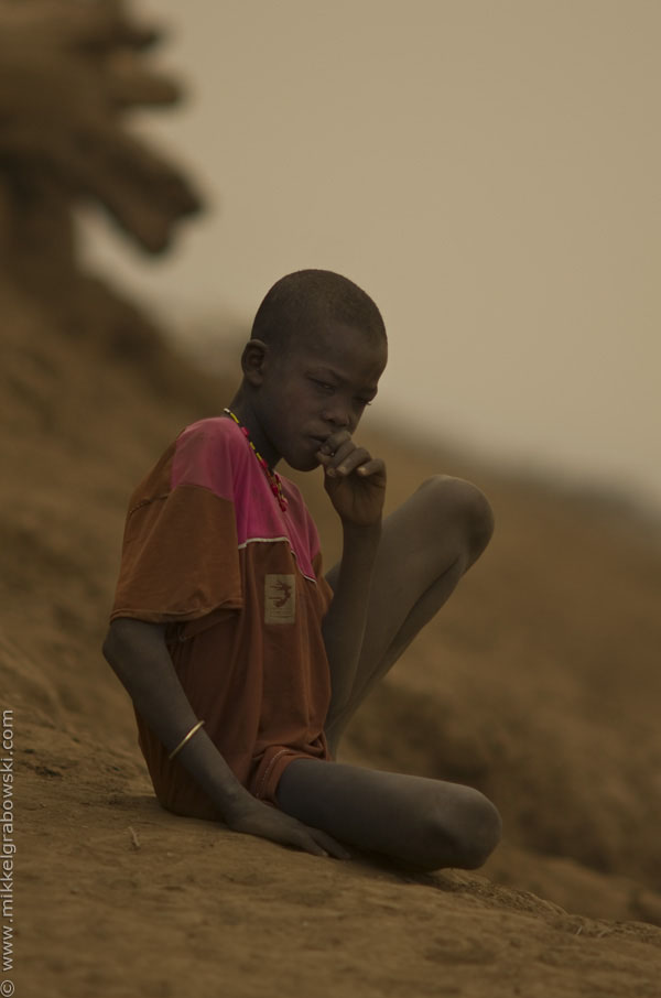 A boy in omorate sits just by the Omo river,  contemplating - photo © Mikkel Grabowski