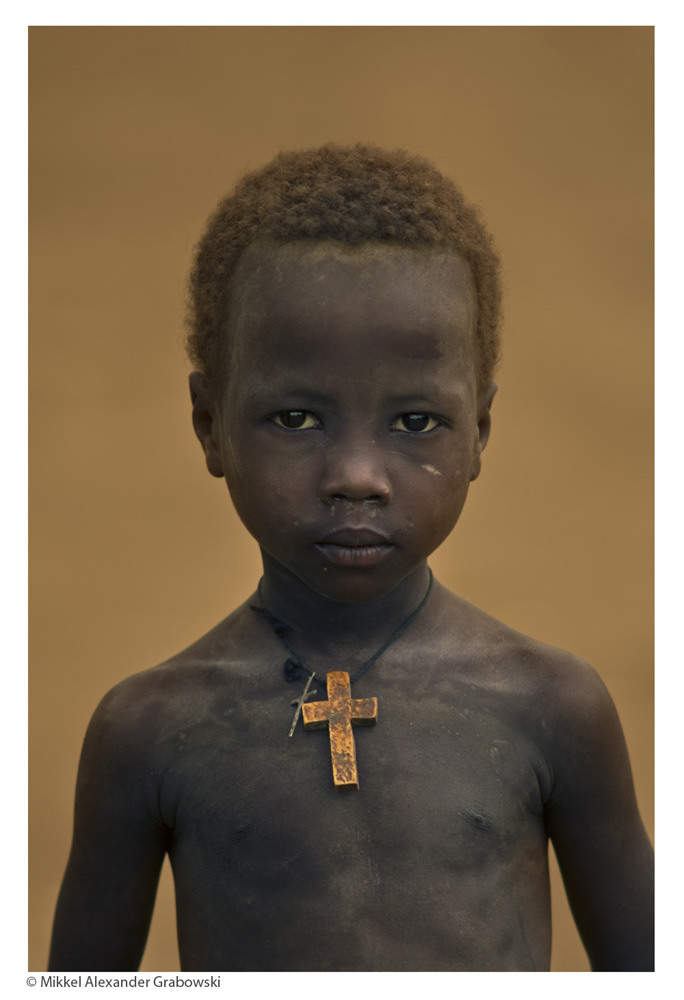 Boy with a wooden cross by the river in Omorate © Mikkel Grabowski