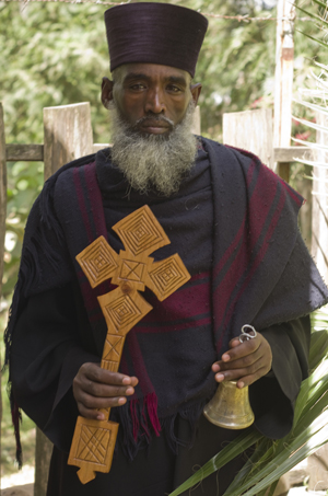 A priest with a cross and a bell