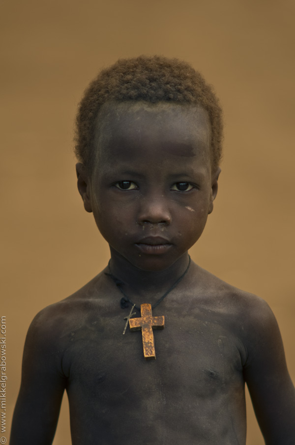 A boy only wearing a cross stands at the bank of the Omo river in southern Ethiopia. Photo © Mikkel Grabowski