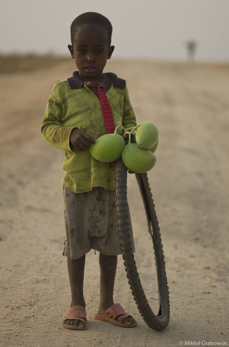Boy playing with a tire and some fruits he uses as a football, Omo valley Ethiopia. Photo © Mikkel Grabowski