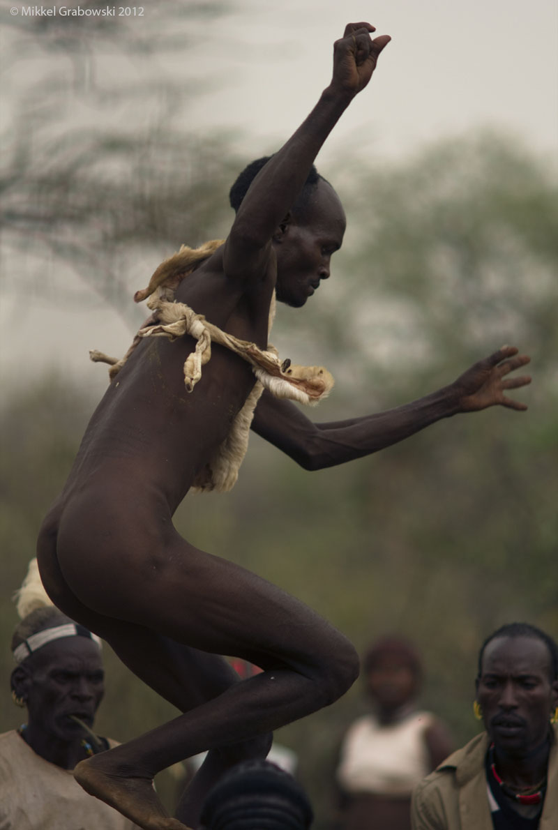 An almost naked man jumping over bulls as part of the bull jumping ceremony by the Hamer tribe in Omo valley. Photo © Mikkel Grabowski 2012