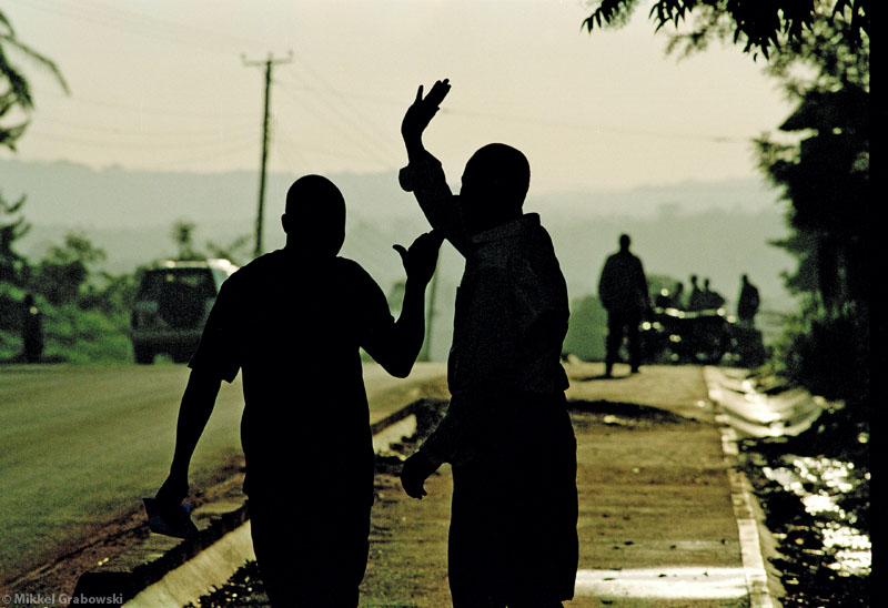 Two road construction workers in Kampala greeting. Photo © Mikkel Grabowski