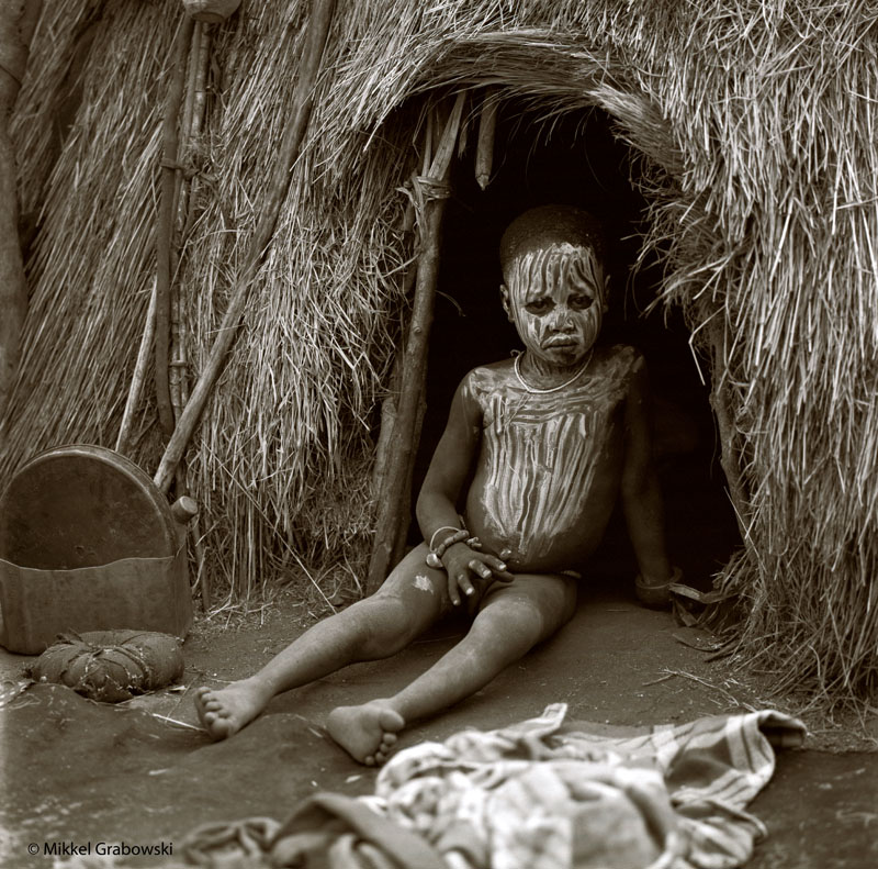 A boy from the Mursi tribe sitting at the entrance of their house in lower Omo valley, Ethiopia - photo © Mikkel Grabowski 2012