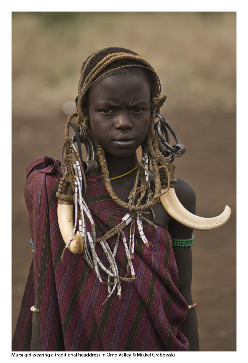A young Mursi girl wearing a treaditional headdress with tuskers from a warthog - photo © Mikkel Grabowski