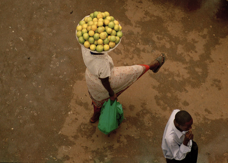 woman with oranges in Kampala making a stop while stretching her leg as a man passes by. Photo © Mikkel Grabowski