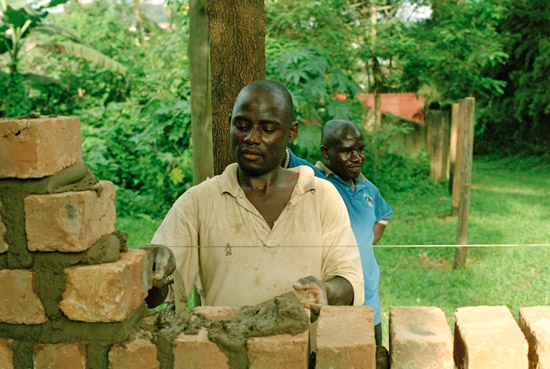 Two men building a brick wall in Kampala