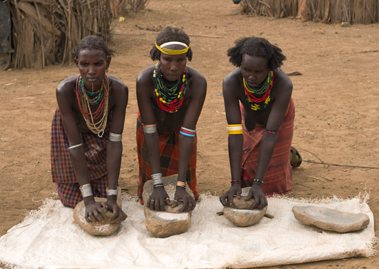 Three women from the Daassanach tribe grinding grains into flour by hand
