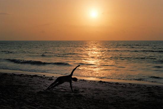 A woman doing yoga on the beach in Paje Zanzibar