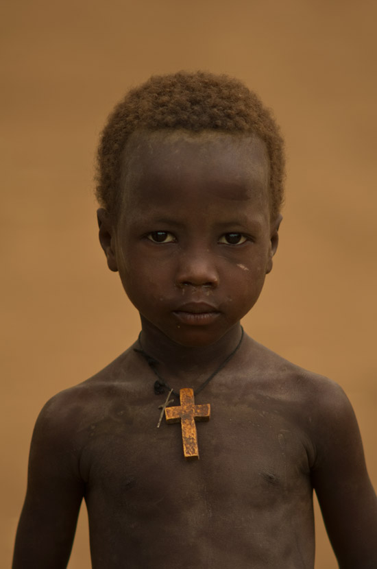 A young boy in Omorate Omo River wearing a cross around his neck