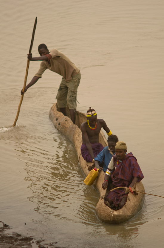 People in a decidely slant shaped canoe, crosses the Omo River in Omorate