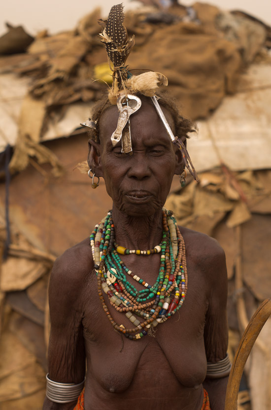 An older Daassanach woman wearing a bottle opener, a feather and beautiful colored pearl necklaces, in Omorate